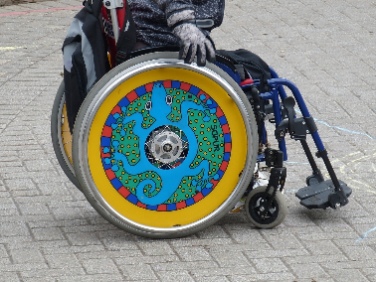 Photo of a child in a wheelchair with colorfull custom wheel covers