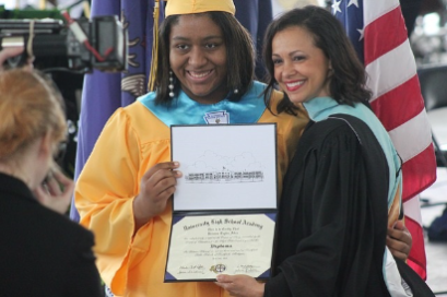 Photo of a girl in a cap and gown recieving her diploma from a woman at graduation