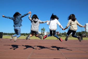 Four Girls jumping while holding hands