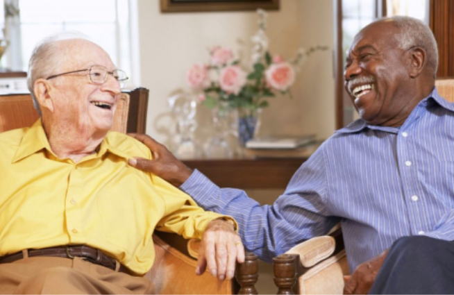 Photo of two elderly men sitting in chairs laughing