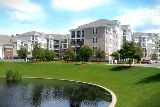 Apartment complex with a lawn and pond in the foreground.