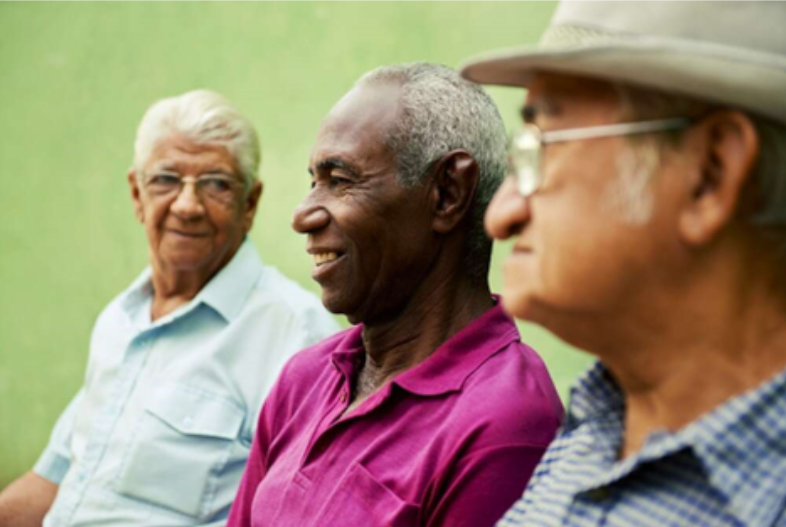 Photo of three elderly men sitting outside
