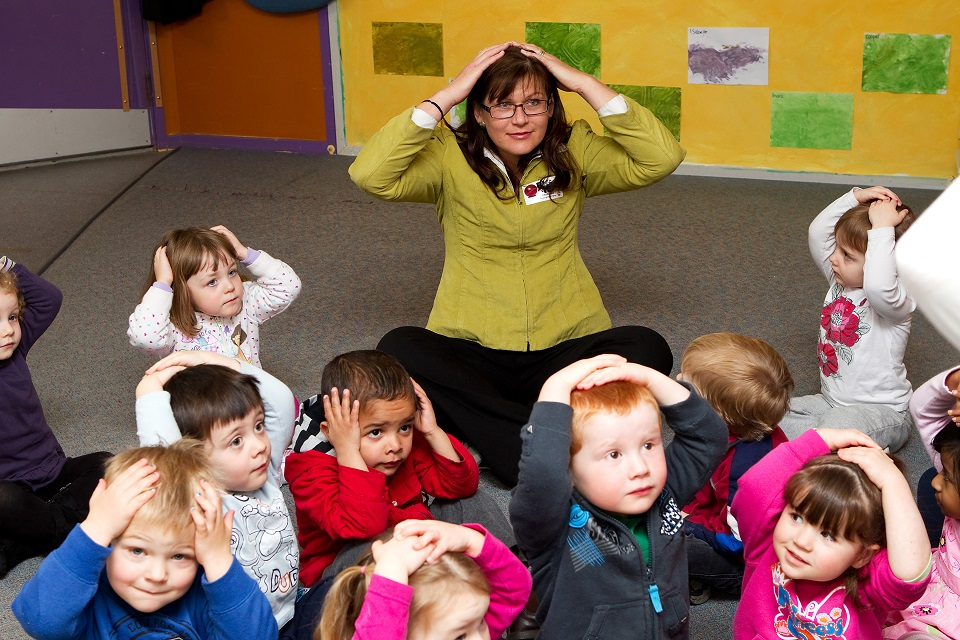 Photo of a teacher and preschool students sitting down on the floor