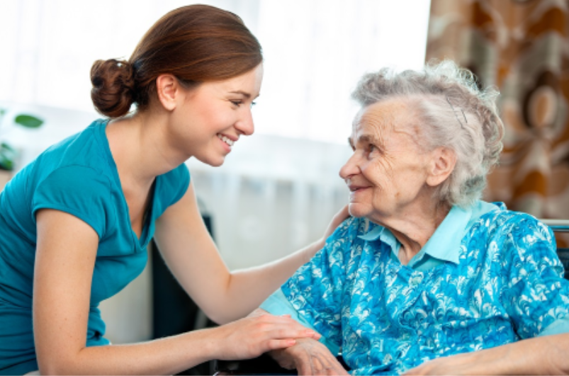 Caregiver in a teal shirt caring for an elderly woman