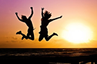 People jumping in front of a beach sunset