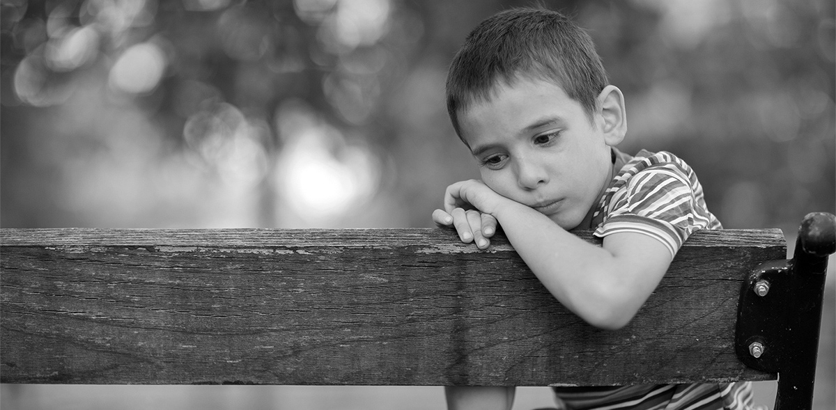 Black and White photo of Little boy on bench