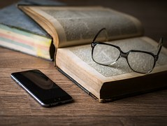 Image of cell phone, glasses and book