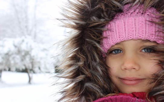 Close up of little girl with a snow background